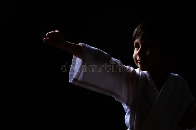 摆在黑暗的背景的白色和服的空手道男孩 孩子准备好武道战斗 战斗在合气道训练的孩子 人兽交 库存图片