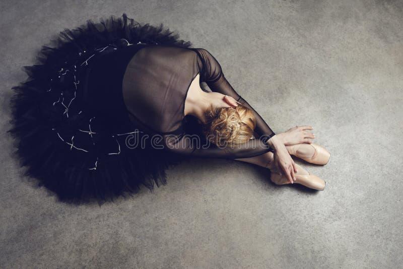 摆在黑背景的一件黑芭蕾舞短裙的芭蕾舞女演员 免版税库存照片