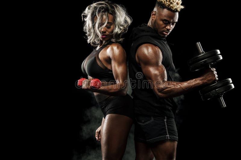 摆在黑背景,健康生活方式身体关心的运动员健身夫妇  与拷贝空间的体育概念 图库摄影