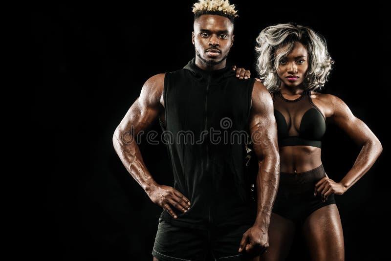 摆在黑背景,健康生活方式身体关心的运动员健身夫妇  与拷贝空间的体育概念 库存图片