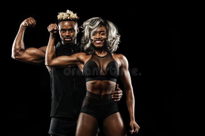摆在黑背景,健康生活方式身体关心的运动员健身夫妇  与拷贝空间的体育概念 免版税库存图片