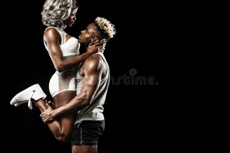 摆在黑背景,健康生活方式身体关心的运动员健身夫妇  与拷贝空间的体育概念 库存照片