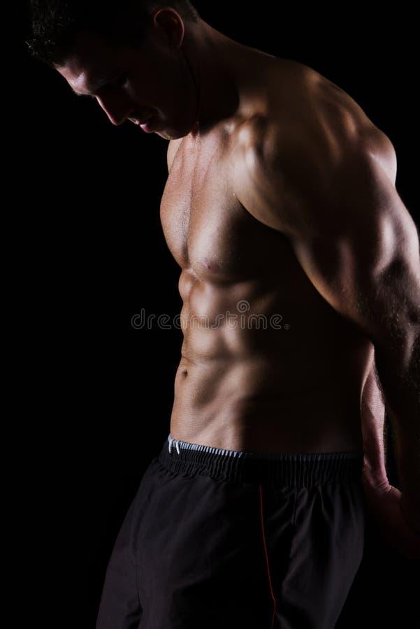 摆在黑色的坚强的肌肉人 免版税库存照片