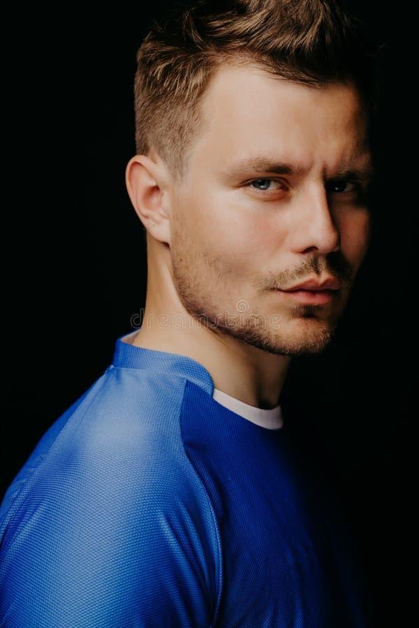 摆在黑黑暗的背景的年轻英俊的足球运动员足球特写镜头画象  库存图片