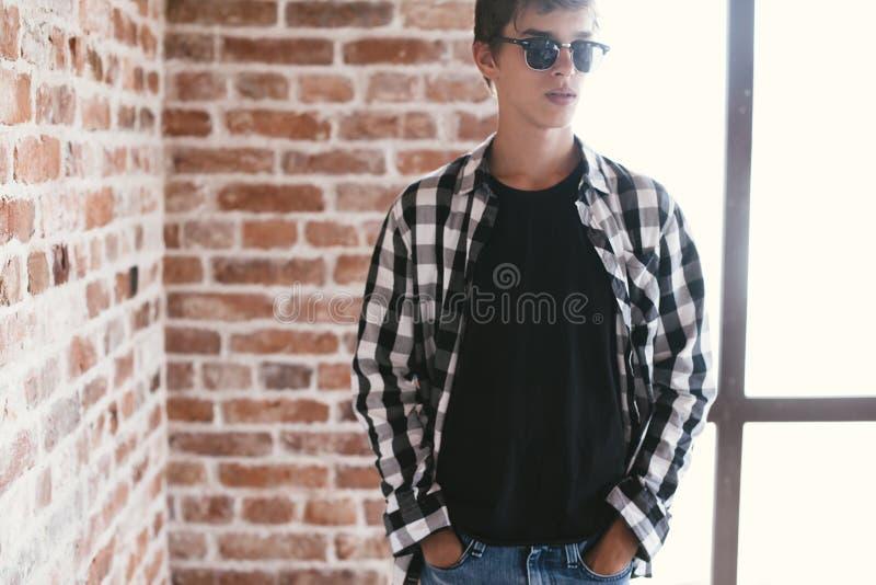 摆在黑T恤杉和太阳镜的行家十几岁的男孩 库存图片