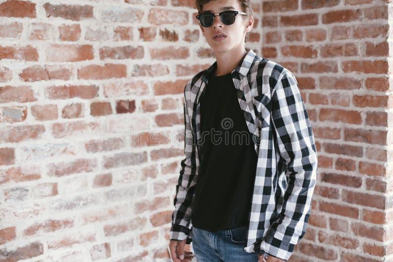 摆在黑T恤杉和太阳镜的行家十几岁的男孩 库存照片