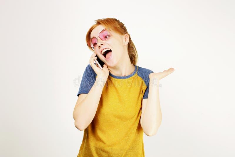 摆在,显示情感表情和做与手机的美丽的红色朝向的少妇滑稽的面孔 免版税库存照片