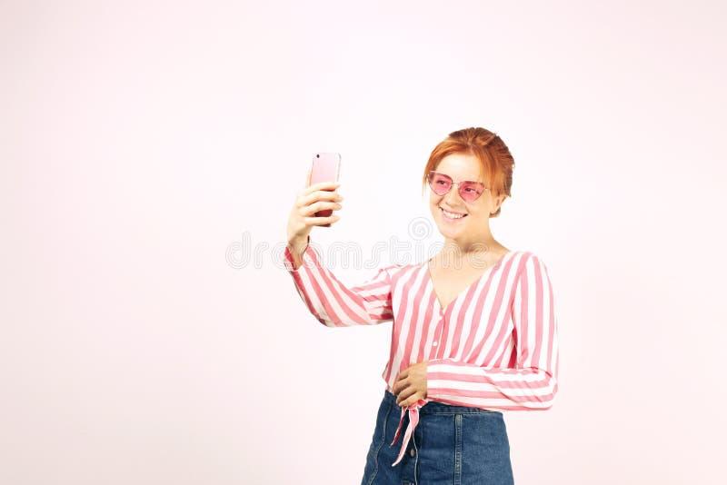 摆在,显示情感表情和做与手机的美丽的红色朝向的少妇滑稽的面孔 图库摄影
