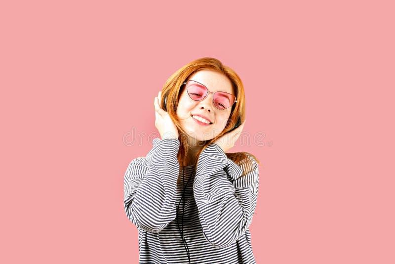 摆在,显示情感表情和做滑稽的面孔的美丽的红色朝向的少妇,跳舞与大耳机 免版税库存图片