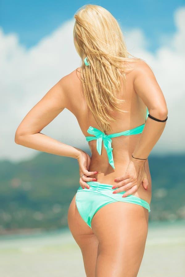 摆在从后面的海滩的女孩,当休息她的胳膊时 免版税库存图片