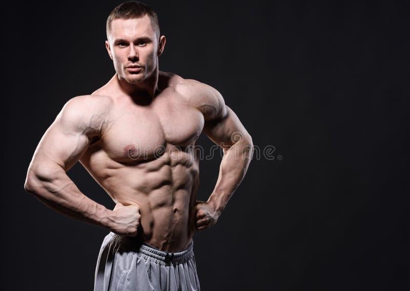 摆在黑暗的背景的演播室的坚强的肌肉人 免版税库存照片