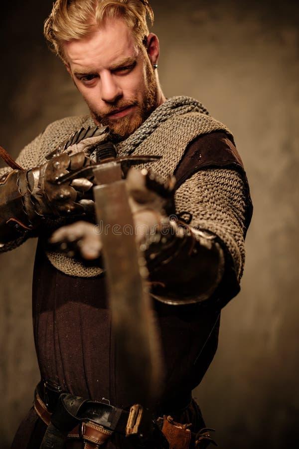 摆在黑暗的背景的年轻中世纪骑士 库存图片