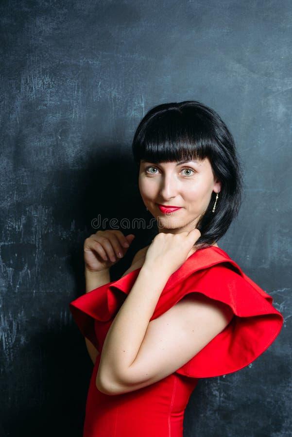 摆在黑板岩的红色礼服的美丽的年轻式样妇女 库存图片