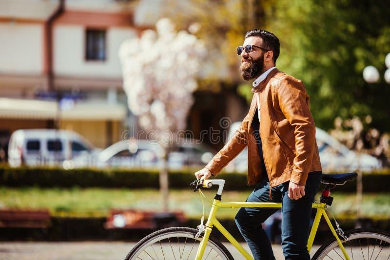 摆在他的在城市街道上的自行车旁边的一个年轻时髦的行家 库存照片