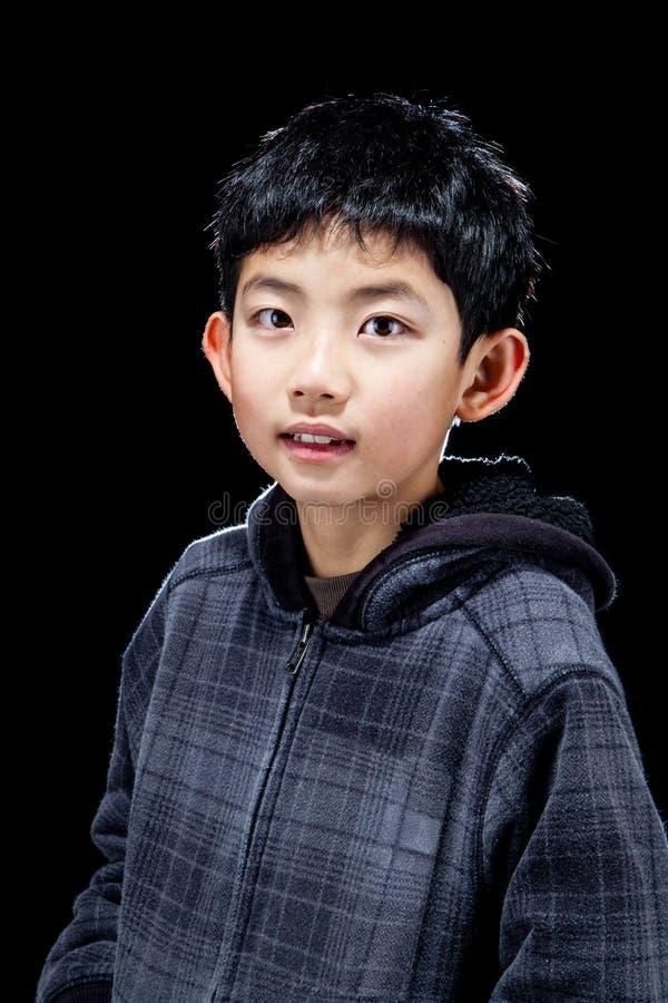 摆在黑背景的逗人喜爱的亚裔男孩在演播室 免版税库存图片