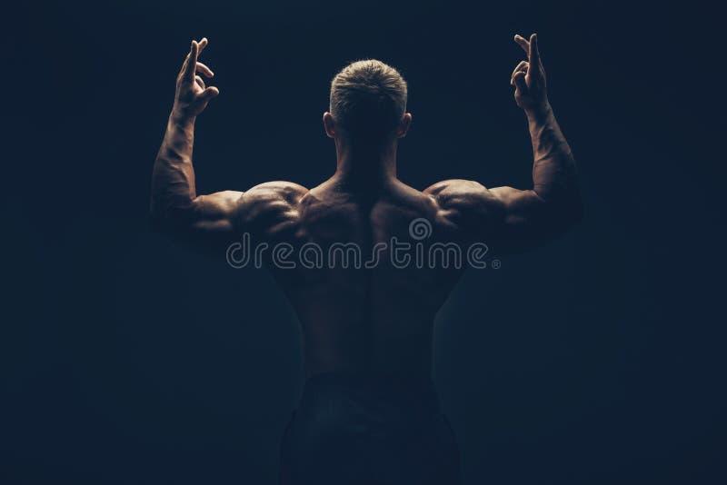 摆在黑色的英俊的肌肉爱好健美者 免版税库存图片
