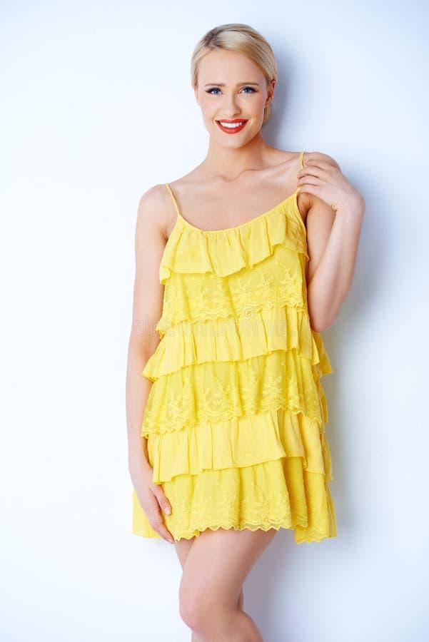 摆在黄色礼服的可爱的白肤金发的少妇 库存照片