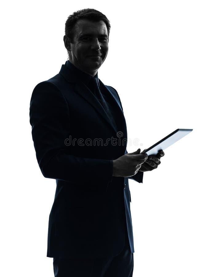 摆在画象剪影的商人数字式片剂 免版税库存图片