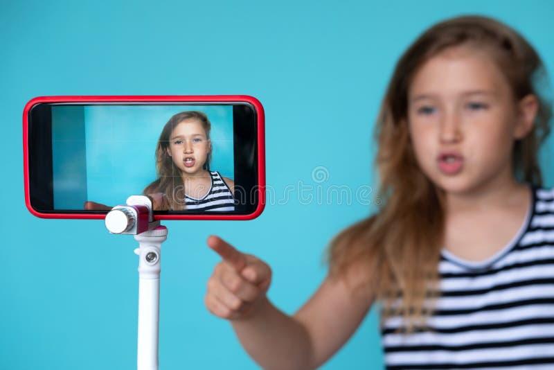 摆在 selfie的电话照相机前面的女孩 免版税库存图片