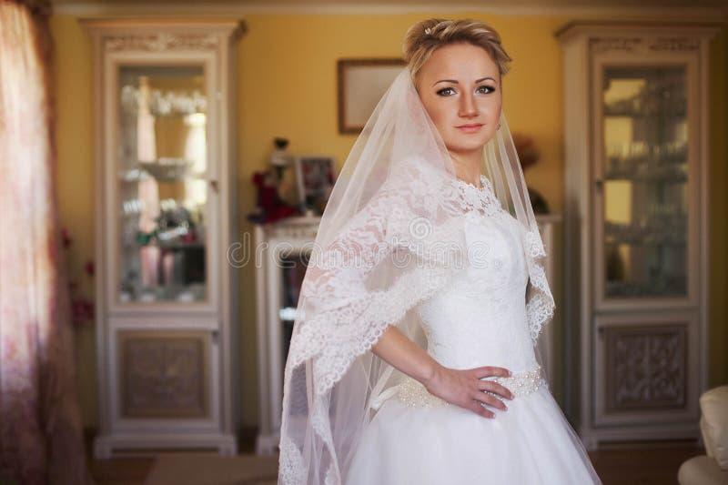 摆在ba的时髦的婚礼礼服的甜年轻白肤金发的新娘 免版税库存图片