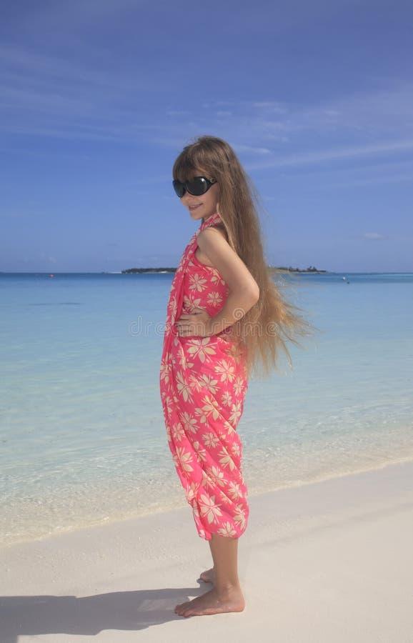 摆在maldivian白色沙滩的女孩 图库摄影