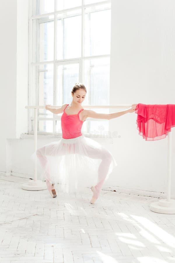 摆在pointe鞋子的芭蕾舞女演员在白色木亭子 免版税库存图片