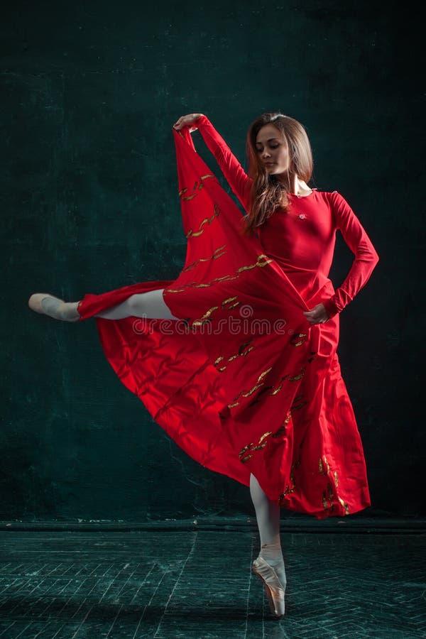 摆在pointe鞋子的芭蕾舞女演员在黑木亭子 免版税库存照片