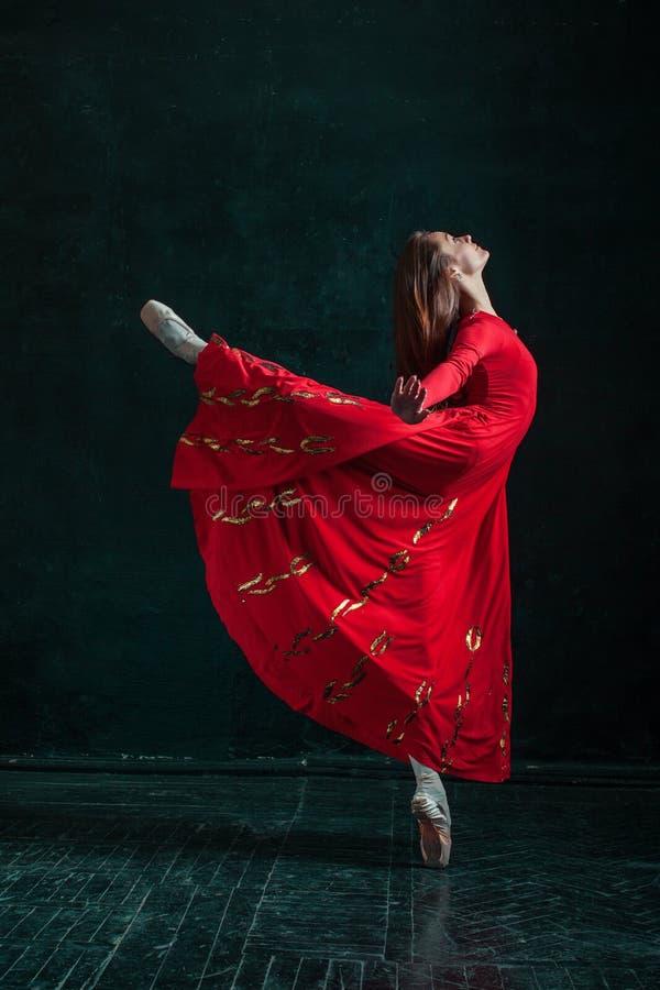 摆在pointe鞋子的芭蕾舞女演员在黑木亭子 库存图片