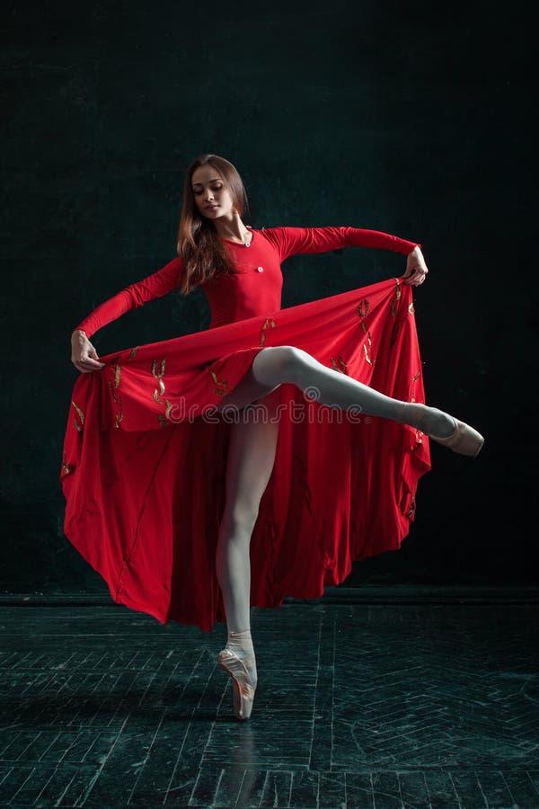 摆在pointe鞋子的芭蕾舞女演员在黑木亭子 图库摄影