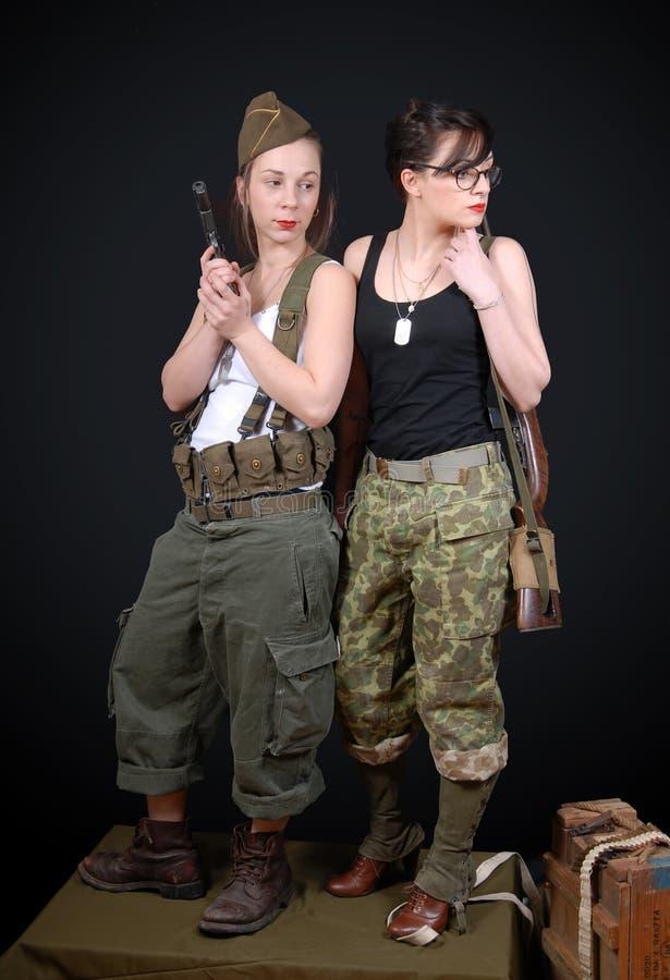 摆在WW2军服和武器的两名性感的妇女 免版税库存图片