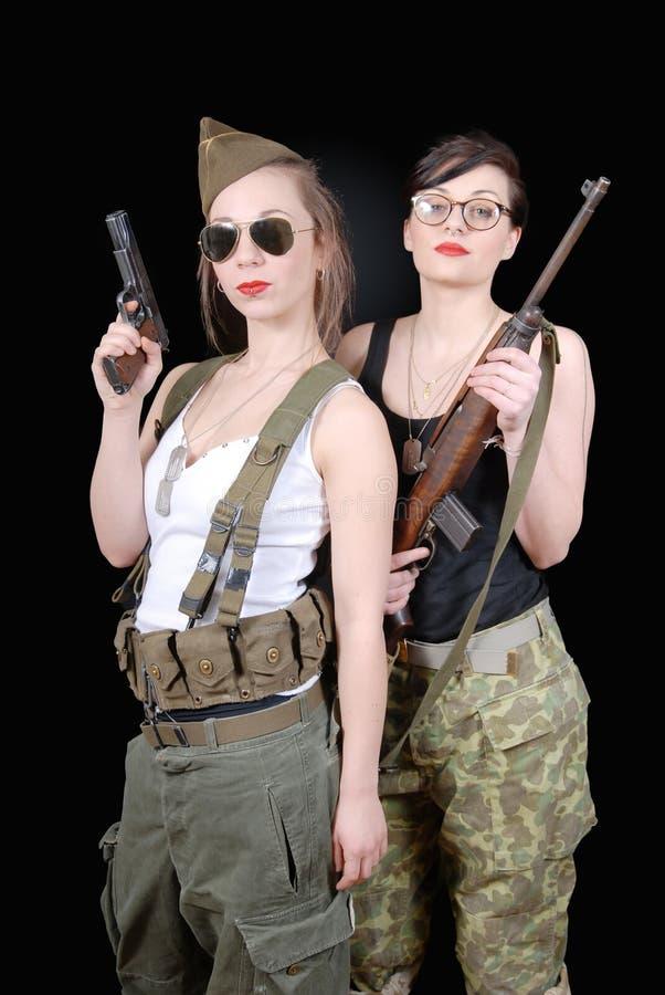 摆在WW2军服和武器的两名性感的妇女 免版税库存照片
