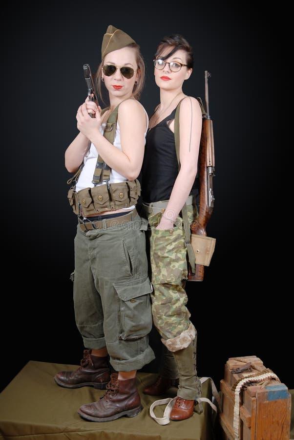 摆在WW2军服和武器的两名性感的妇女 图库摄影
