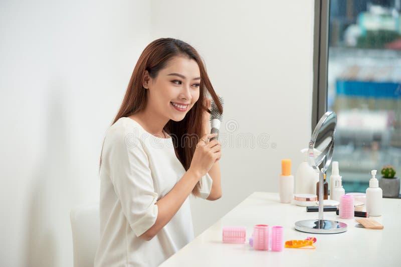 摆脱缠结 看她的在mirrorand的美丽的年轻女人反射掠过她的长发,当坐在时 免版税库存图片