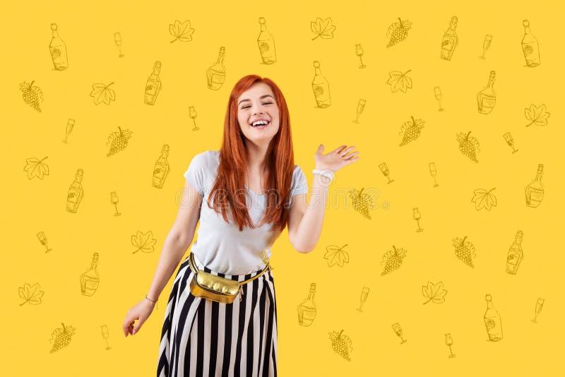 摇她的手的愉快的女孩,当招呼朋友时 免版税图库摄影