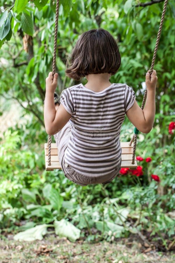摇摆后面的观点的逗人喜爱的孩子放松夏令时 免版税库存照片