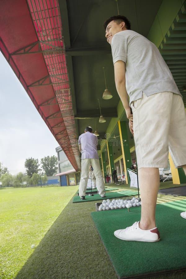 摇摆和击中在高尔夫球场的年轻人高尔夫球 免版税图库摄影