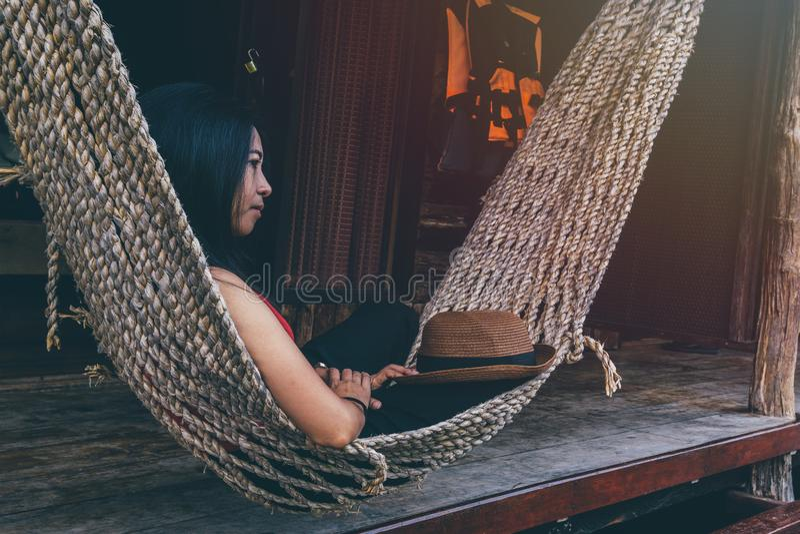 摇摆在一个周末晚上的宜人的懒惰的一个吊床的年轻白种人亚裔女孩 免版税图库摄影