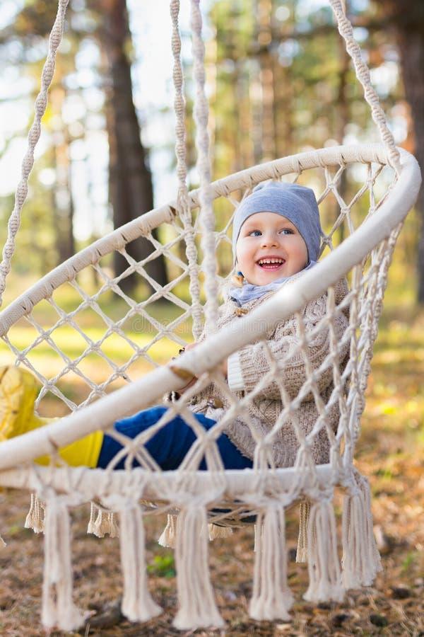摇摆在一把垂悬的椅子的愉快的孩子在森林里 库存图片