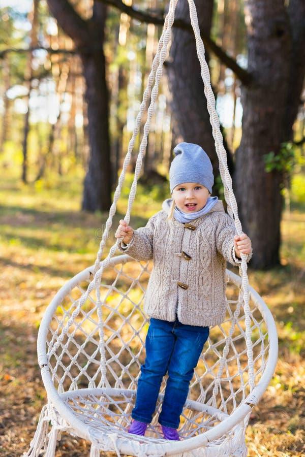 摇摆在一把垂悬的椅子的愉快的孩子在森林里 库存照片