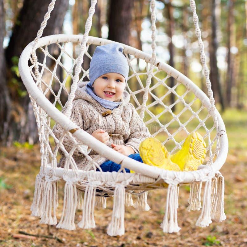 摇摆在一把垂悬的椅子的愉快的孩子户外 免版税库存照片