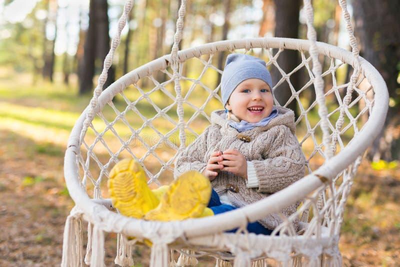 摇摆在一把垂悬的椅子的愉快的微笑的孩子在森林里 免版税库存照片