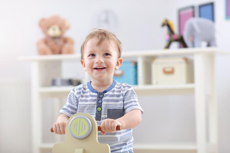 摇摆在一把摇椅的快乐的男婴以滑行车的形式 图库摄影