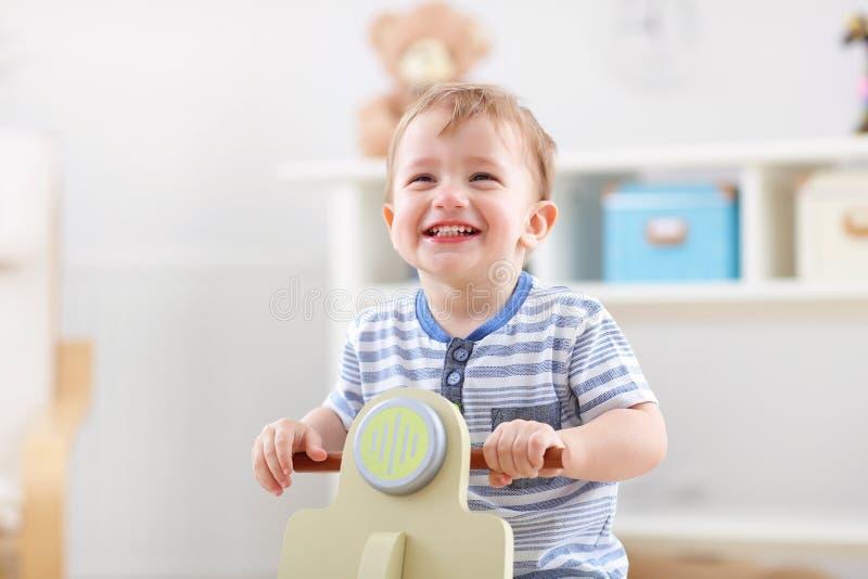 摇摆在一把摇椅的快乐的男婴以滑行车的形式 库存图片