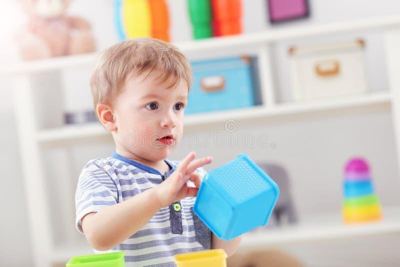 摇摆在一把摇椅的快乐的男婴以滑行车的形式 免版税库存照片