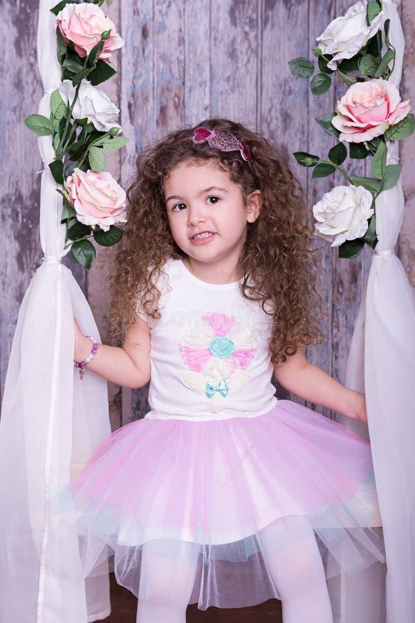 摇摆在与花的一个摇篮的逗人喜爱的甜小女孩 免版税库存照片