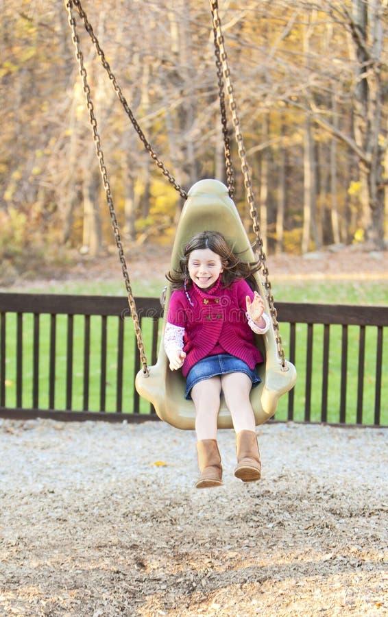 摇摆在公园的俏丽的女孩 免版税库存照片