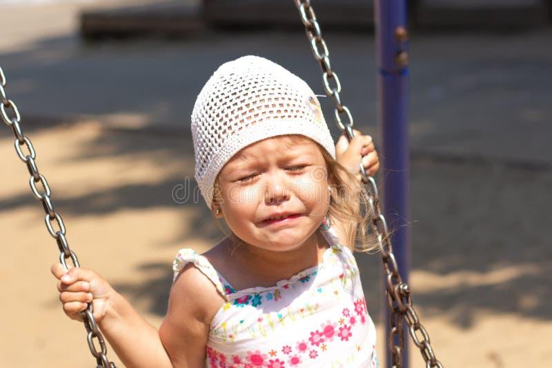 摇摆在夏天公园的哭泣的女孩 库存照片