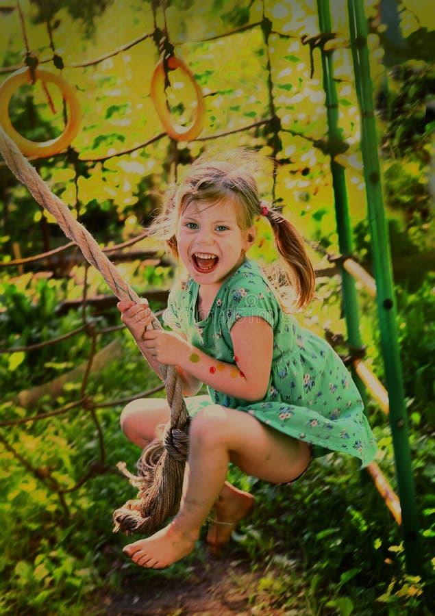 摇摆在夏天戏剧的缆绳绳索的小白肤金发的女孩 库存图片