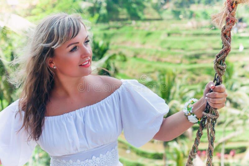 摇摆在摇摆,米大阳台的愉快的妇女 旅行在巴厘岛 免版税库存图片