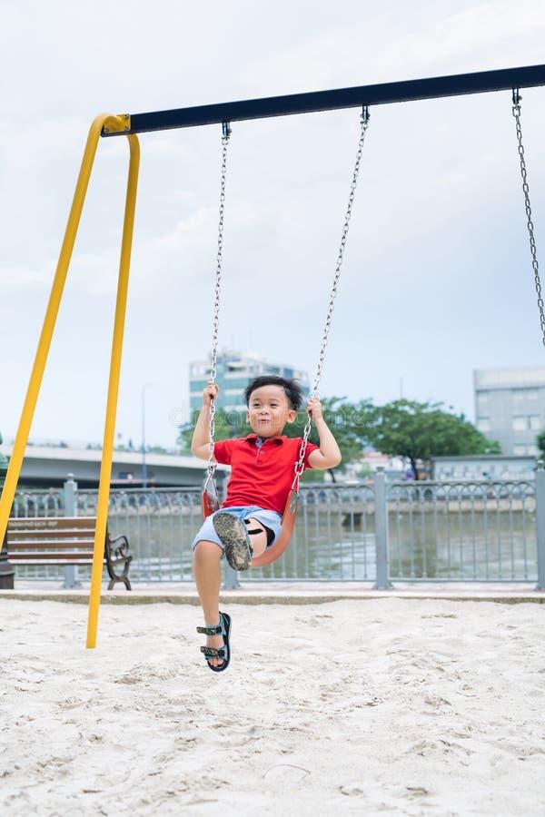 摇摆在操场的愉快的亚裔男孩在公园 免版税图库摄影
